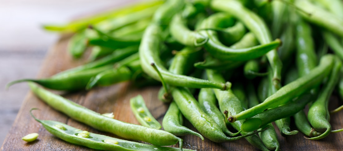 A pile of fresh green beans on a cutting board.