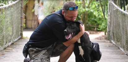 A man hugging a black and white lab mix.