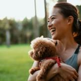Young woman holding a mini goldendoodle in a park.